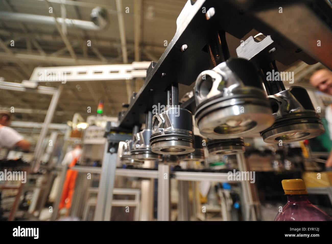 Inside a modern car factory, vehicles and parts move through the production process, pistons ready to be fitted Stock Photo