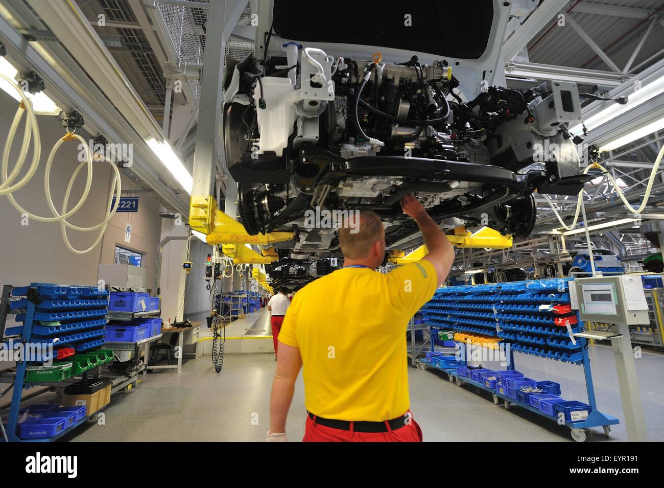 Inside a modern car factory, vehicles and parts move through the production process, workers under the raised car - Stock Image