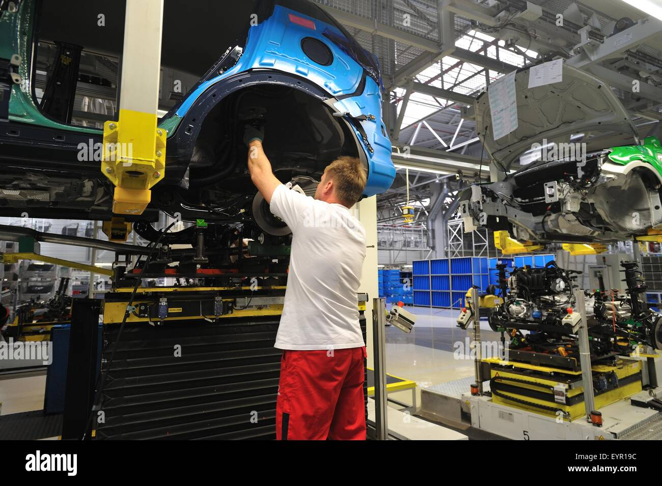 Inside a modern car factory, vehicles and parts move through the production process on a constantly moving production - Stock Image