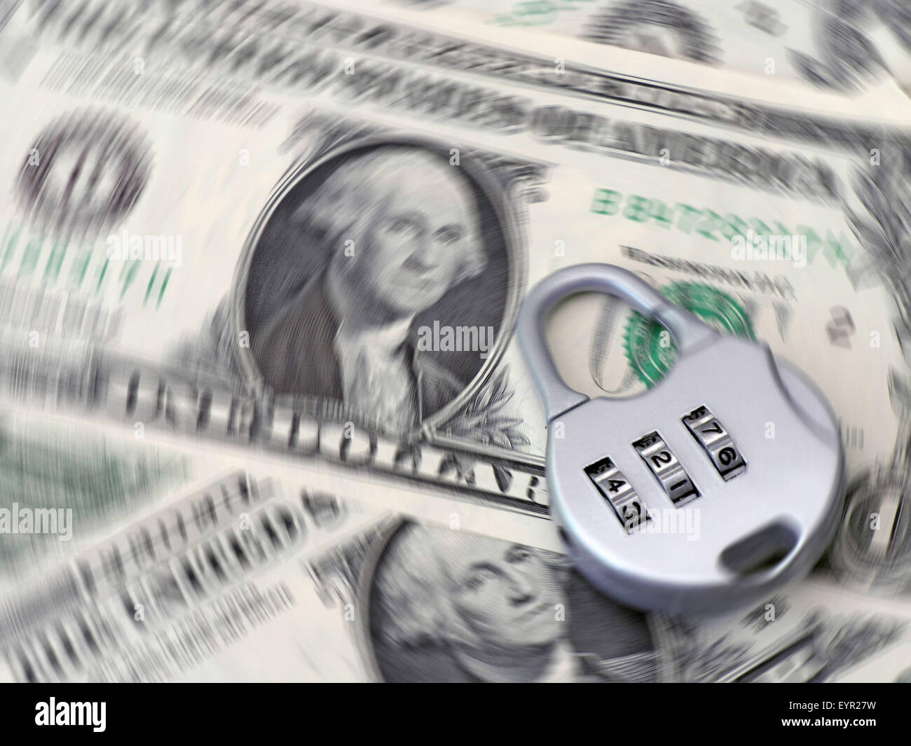 Combination padlock rests on US dollar banknotes with spin effect - Stock Image