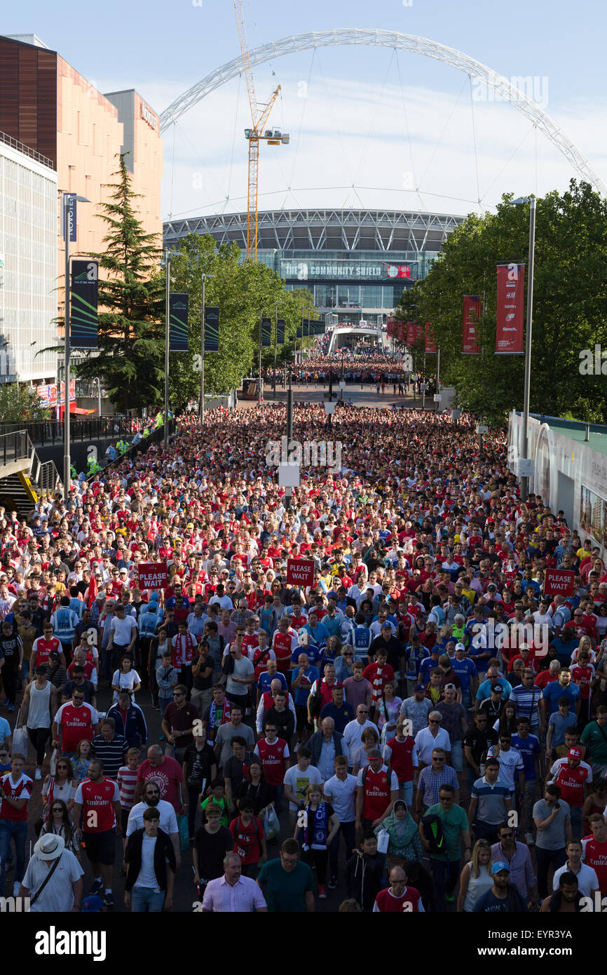 Wembley Stadium with football supporters in the foreground walking to Wembley Park tube station - Stock Image