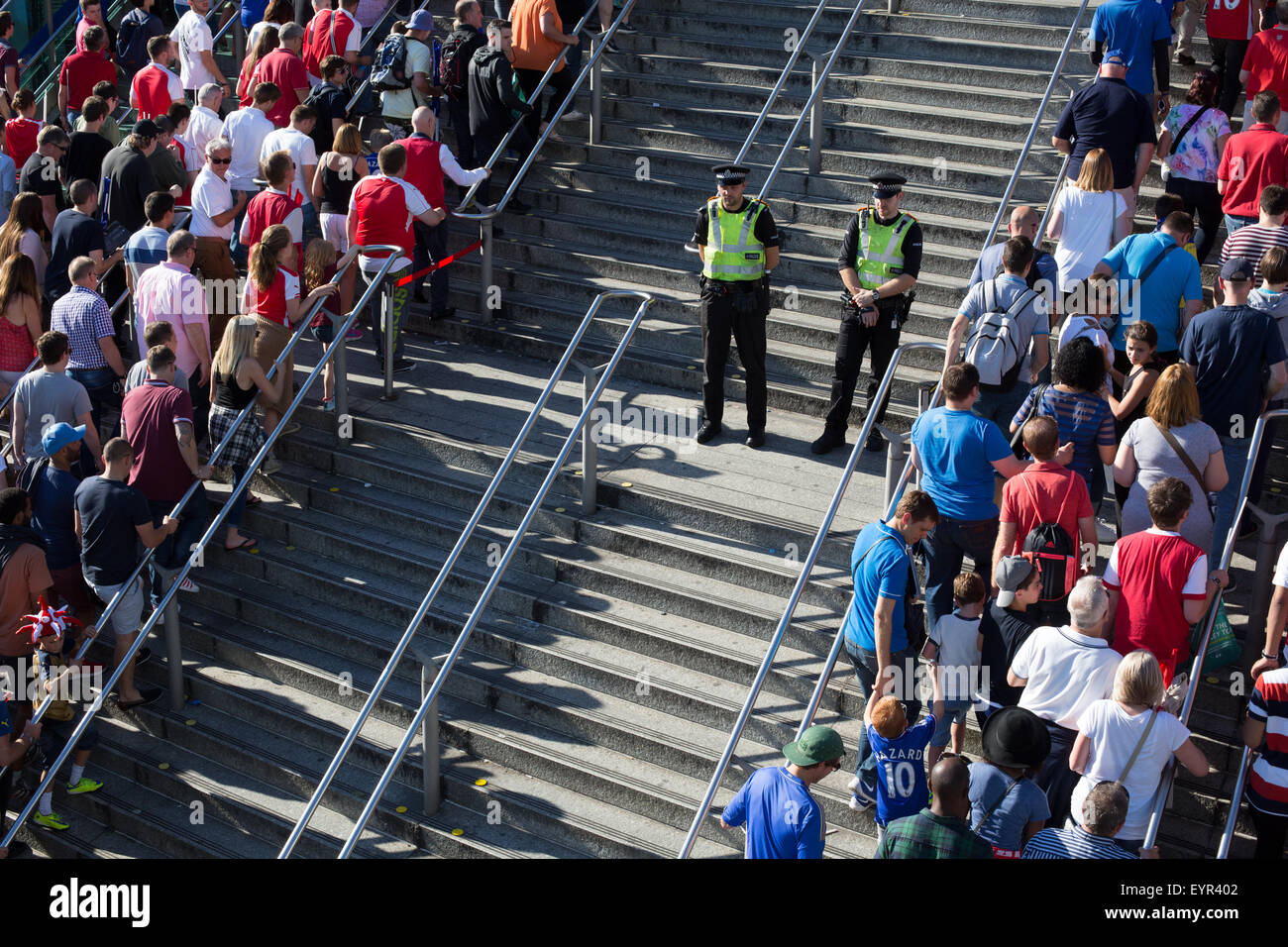 Police stand between football supporters heading to a station following a match at Wembley Stadium - Stock Image