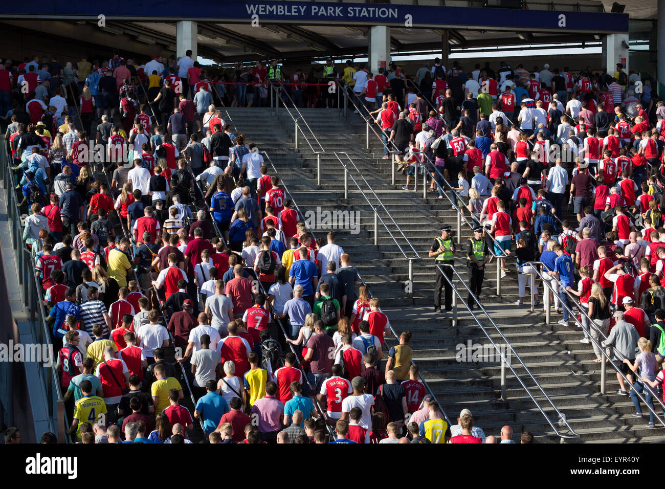 Football supporters climb steps heading into Wembley Park Tube Station after the 2015 Community Shield Arsenal v - Stock Image