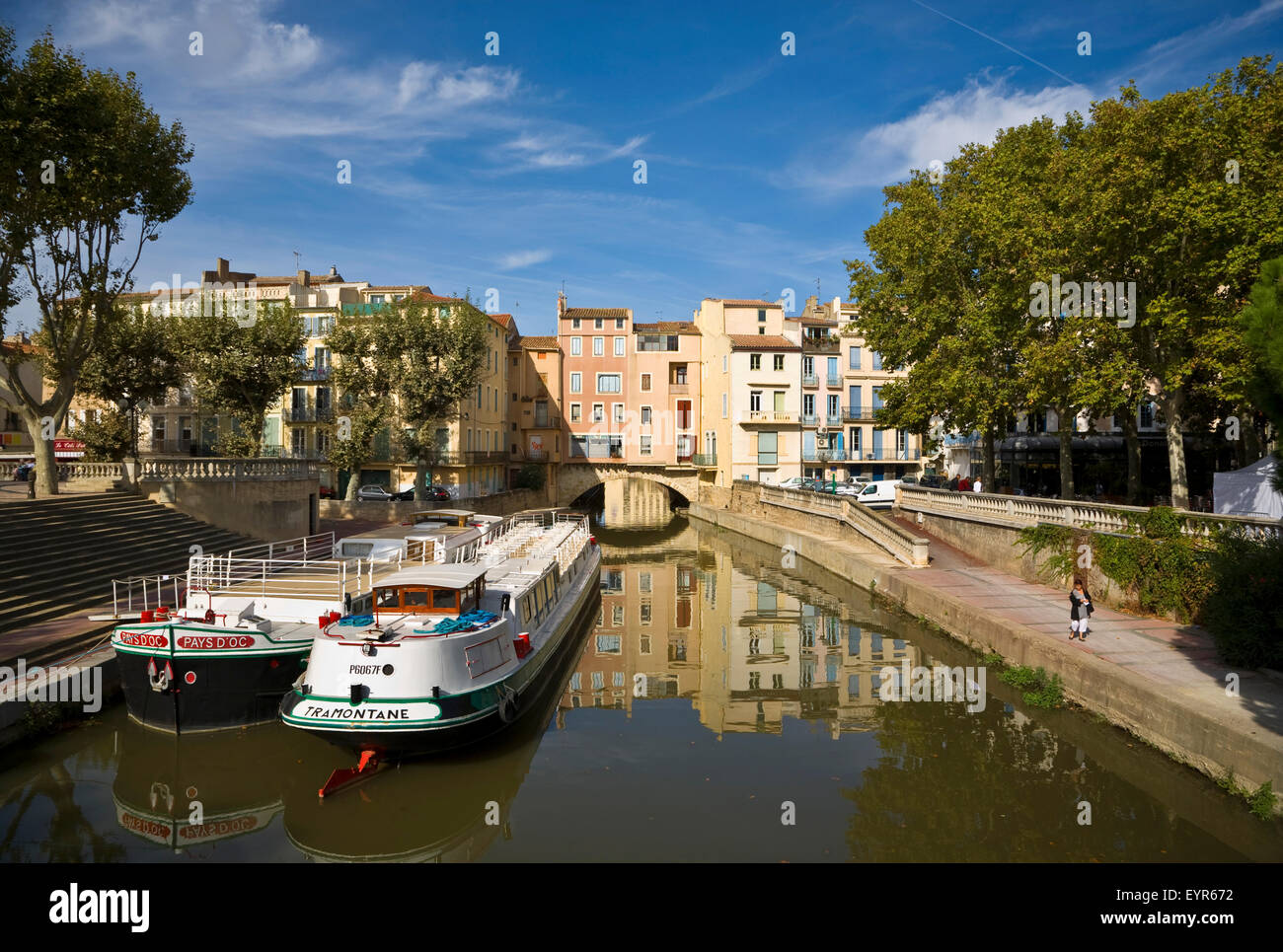 Barges on the Canal du Midi as it runs under the 1st Century Pont de Marchands inhabited bridge in Narbonne, Languedoc - Stock Image