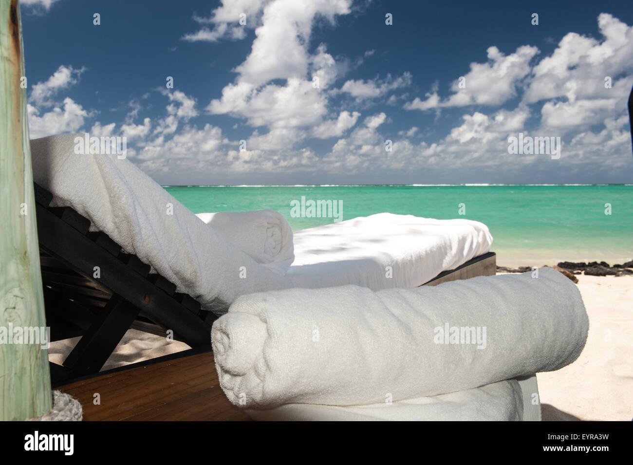 Ile au Cerfs, Mauritius. White towels on sun lounger with a tourquoise sea. - Stock Image