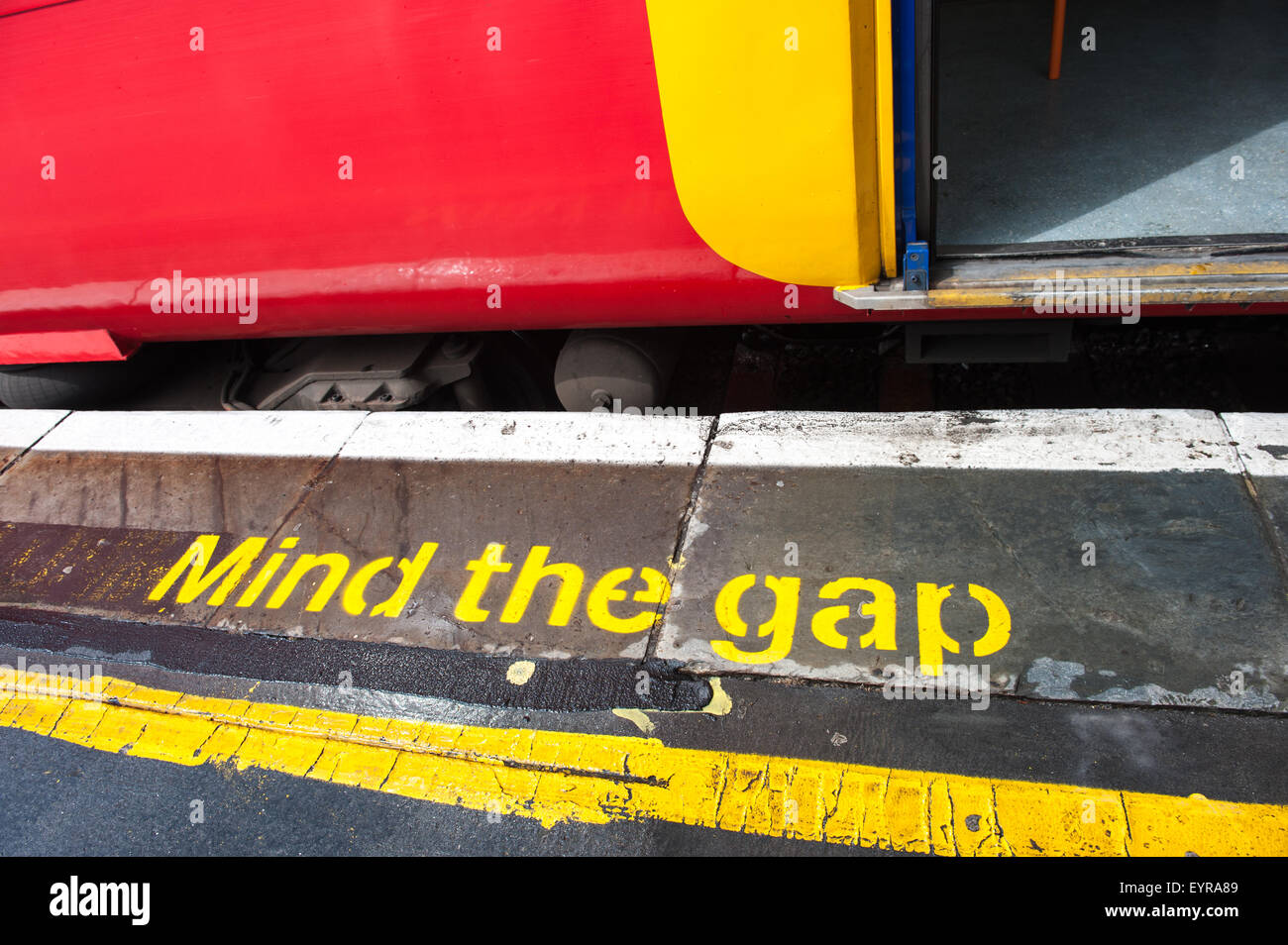 "London England. Colourful South West train and platform with ""Mind the Gap"" in yellow. Stock Photo"