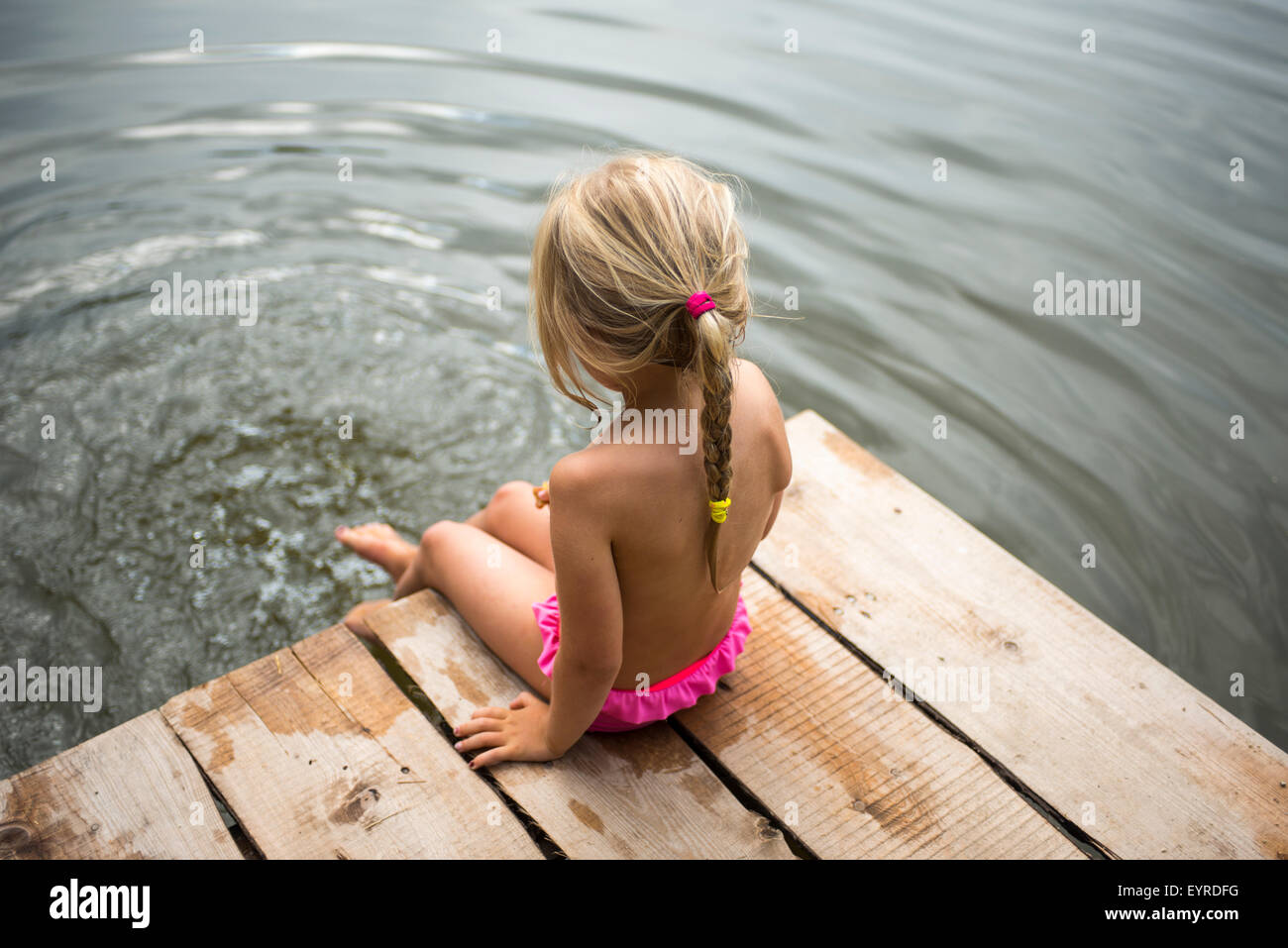 Rear view of child blond girl sitting on pier looking at view of pond with her feet in the water - Stock Image
