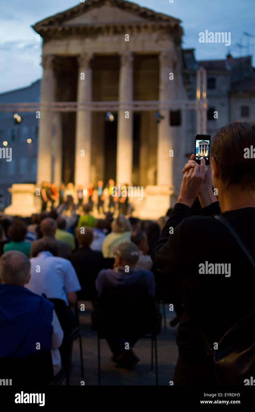 Tourist Taking Snapshot with Smartphone of an Evening Cultural Program Vertical - Stock Image