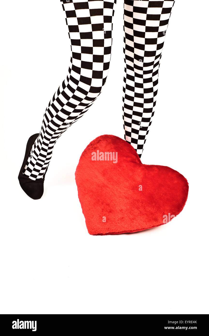 legs of a woman in checkered knee high socks and a red heart shaped cushion - Stock Image
