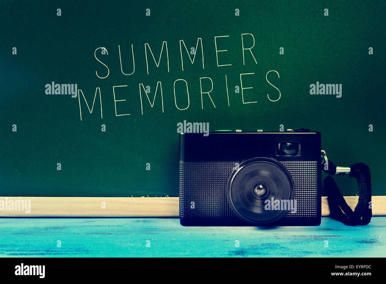 a retro camera on a rustic blue wooden surface and the text summer memories written on a green chalkboard, with - Stock Image