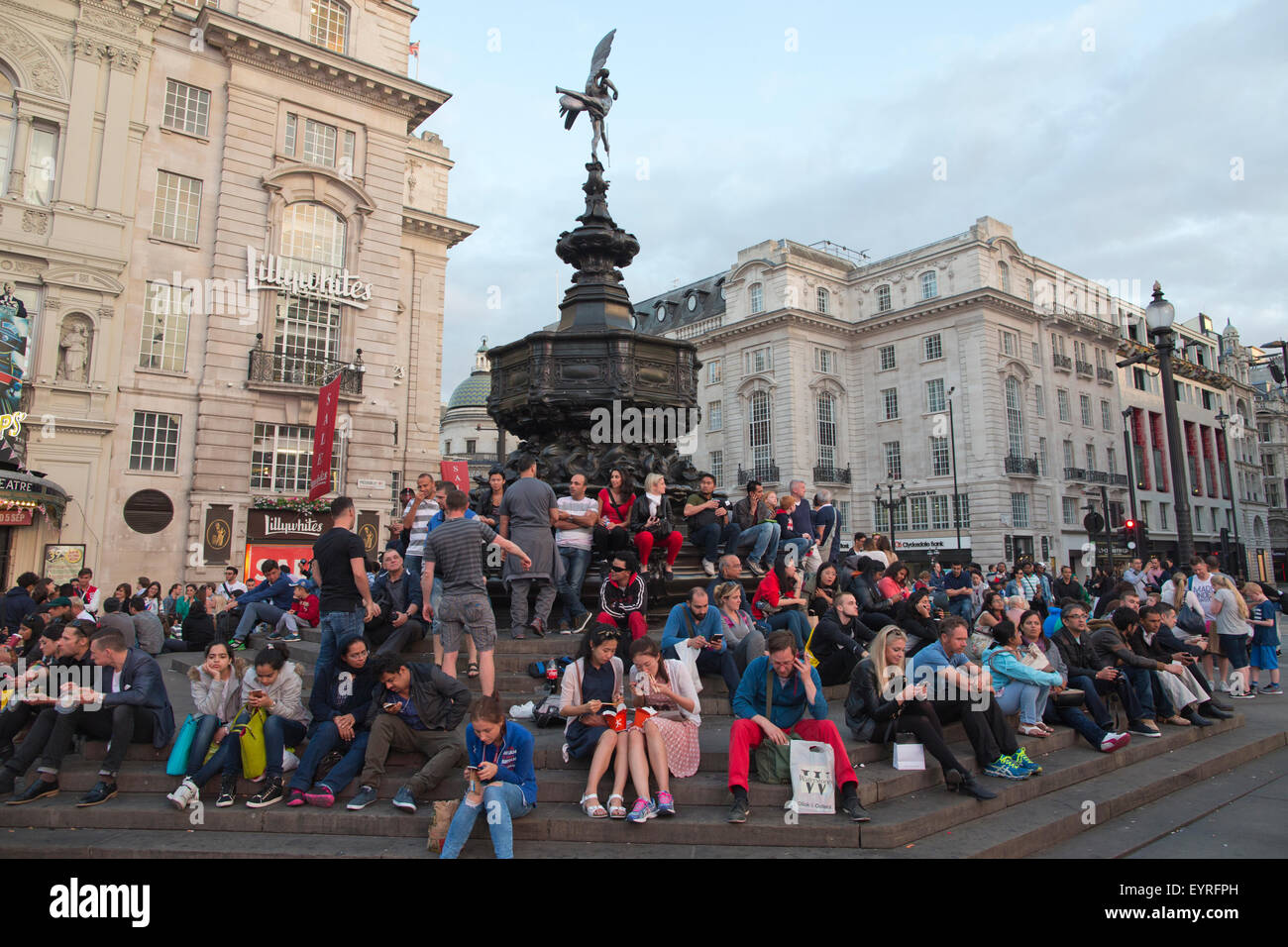 Tourists sitting on the steps of the Shaftesbury Memorial Fountain and statue of Eros, Piccadilly Circus, London, - Stock Image