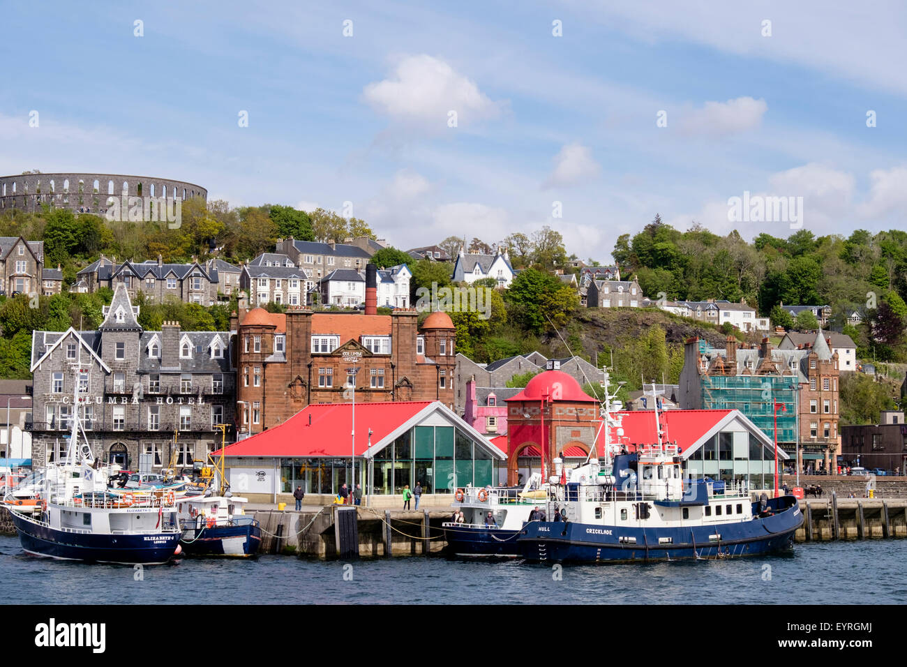 Boats moored by the pier with McCaig's tower folly on hill above in Oban, Argyll and Bute, Scotland, UK, Britain - Stock Image