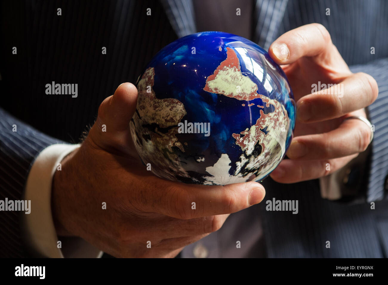 London, England. A businessman in a suit holds, turns a colourful globe in his hands. The world spins. - Stock Image