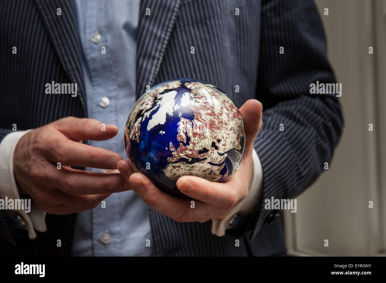 London, England. Businessman holding a globe of the Earth made of semi-precious stones. - Stock Image