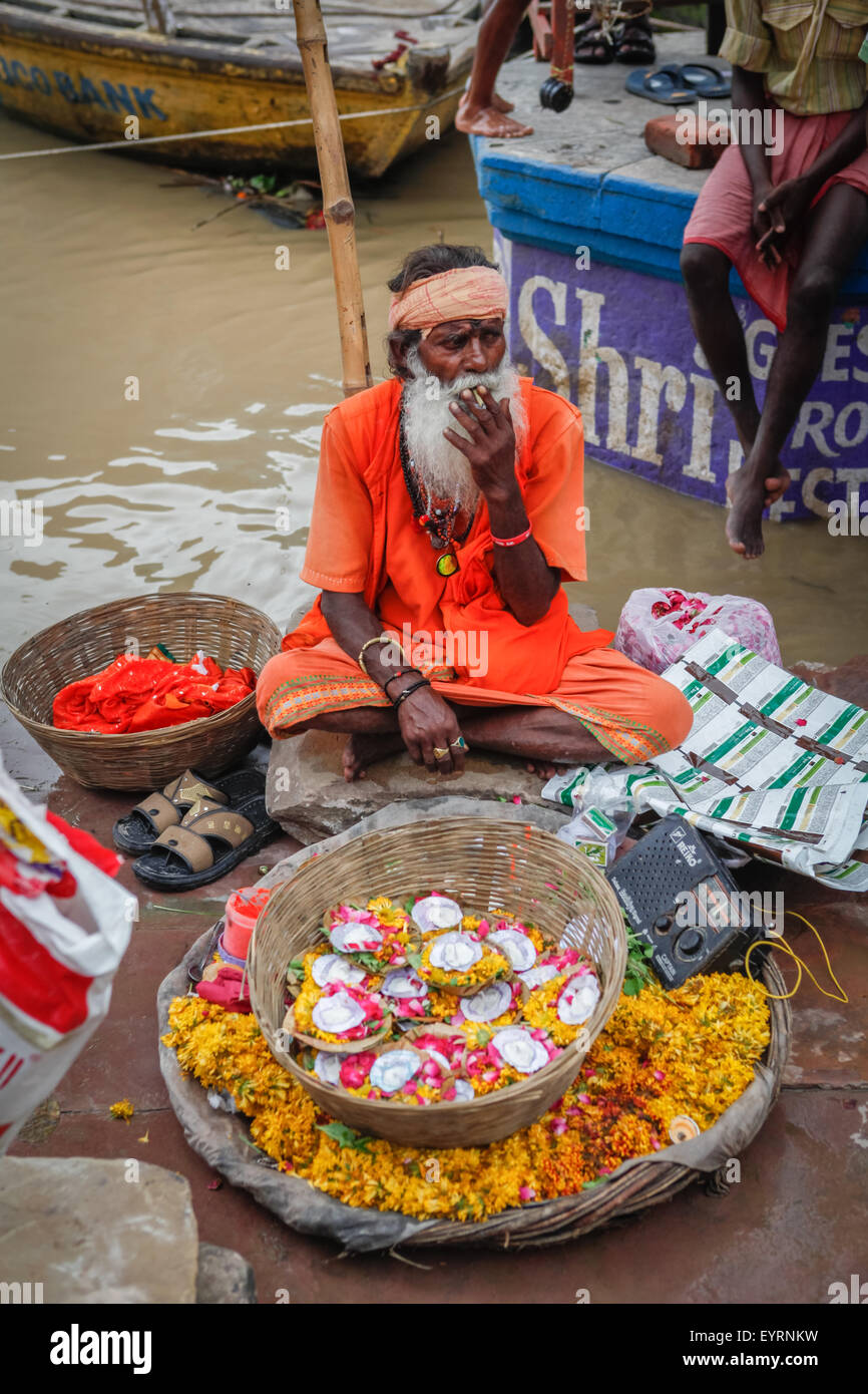 Sadu selling flowers at Dashashwamedh Ghat. - Stock Image
