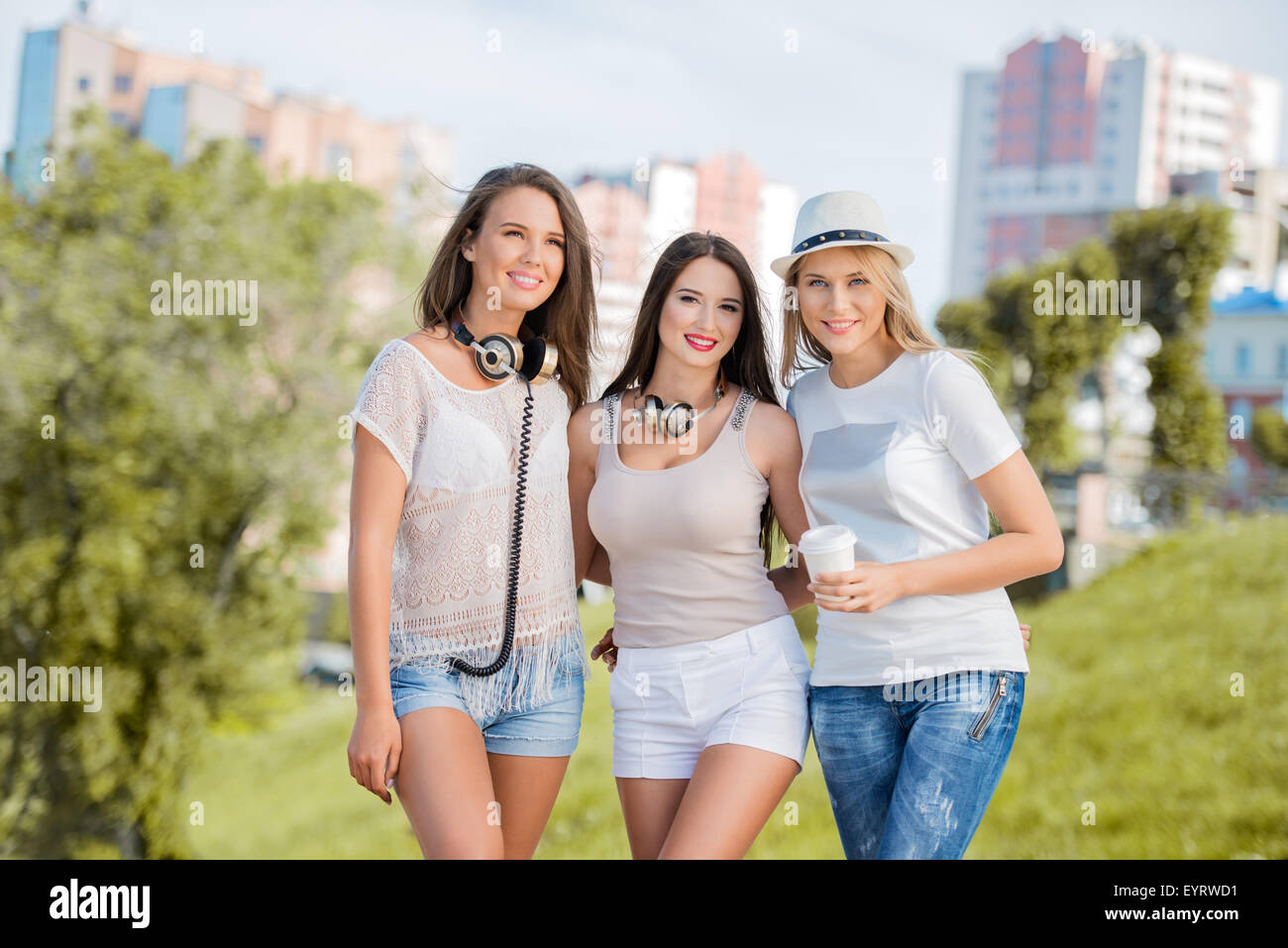 Three happy young women with vintage music headphones and a