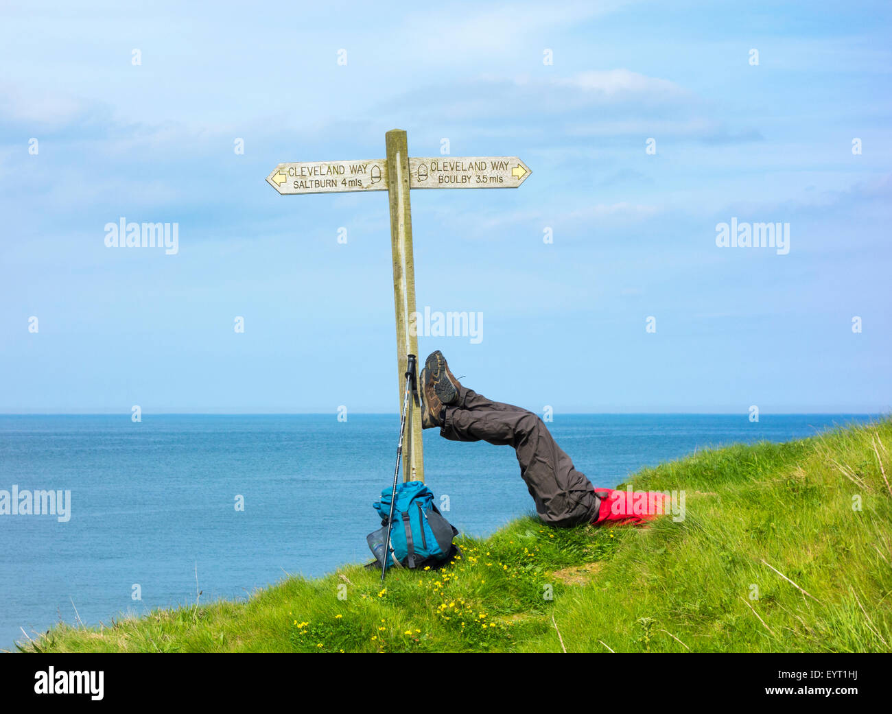 Male hiker resting with feet on signpost at Skinningrove between Saltburn and Staithes on The Cleveland Way trail. - Stock Image