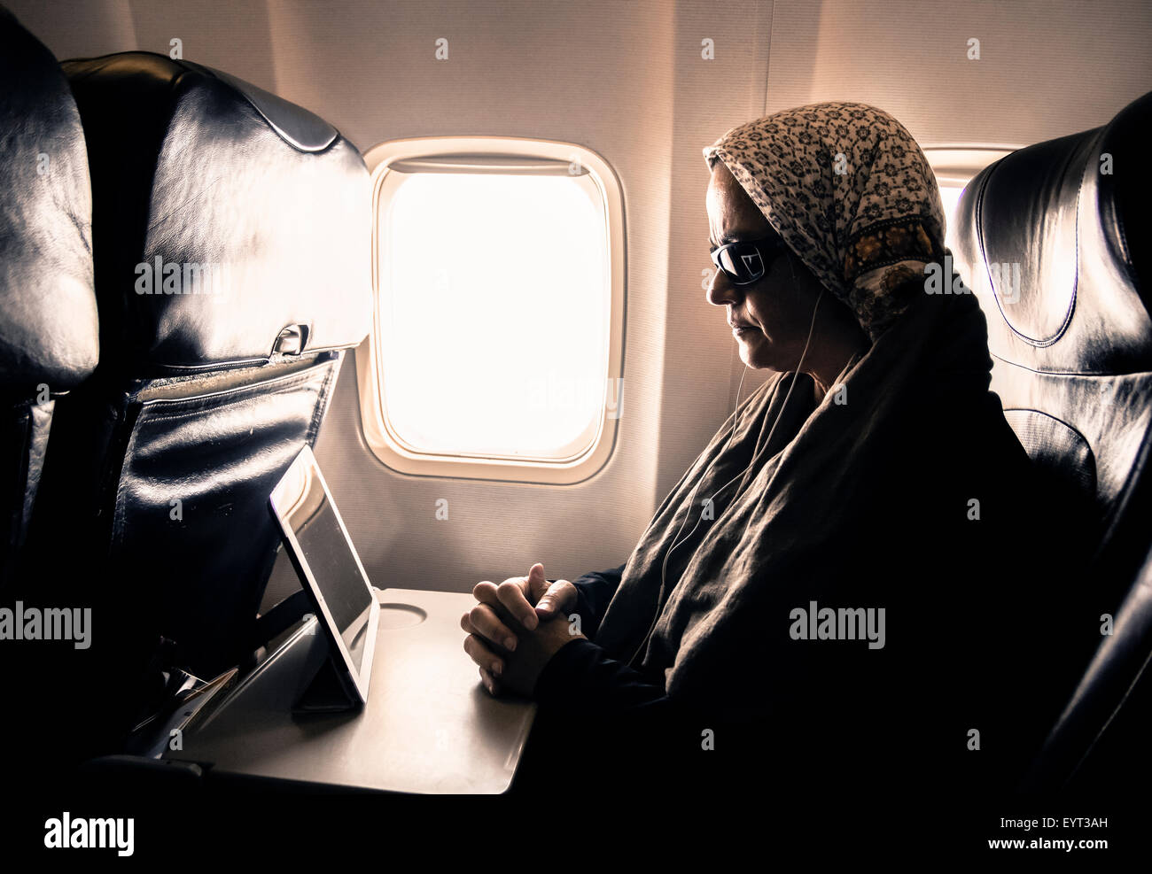 Woman reading book on tablet device in airplane window seat - Stock Image