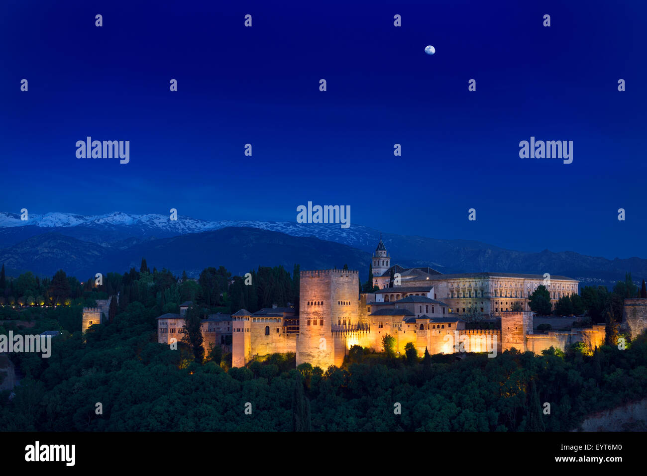 Moonrise over lit hilltop Alhambra Palace fortress complex at twilight Granada with snow capped Sierra Nevada Mountains - Stock Image