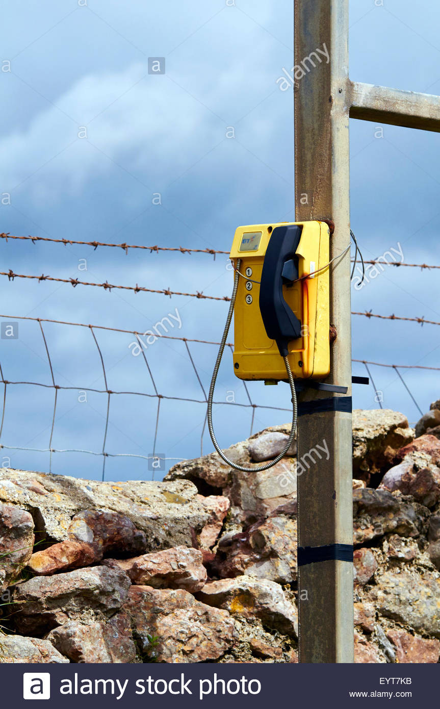 yellow and black emergency telephone on a wooden post on the welsh wales coastal path - Stock Image