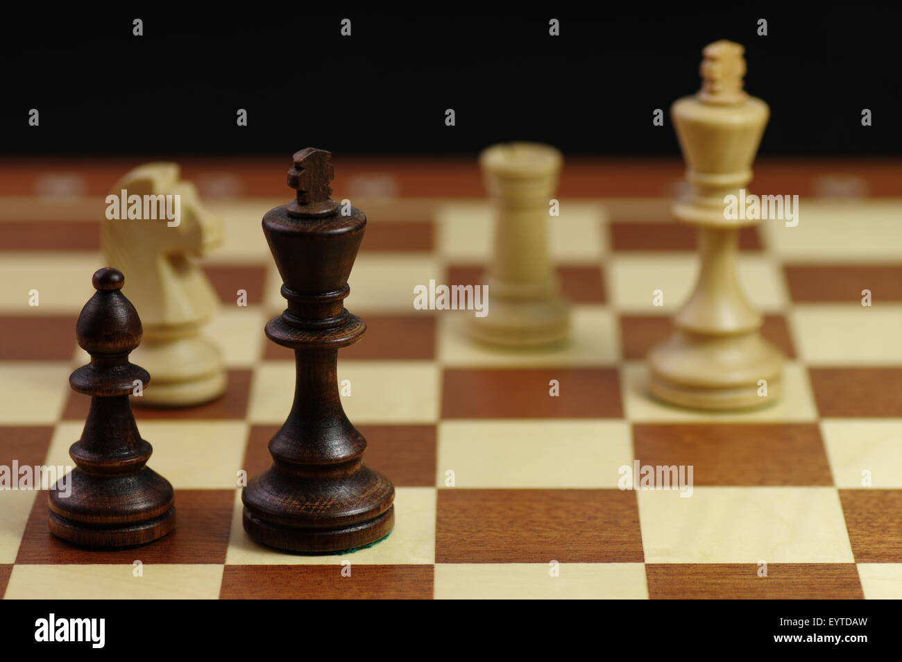 Chess game. Ending chess party.  Black king in check, but still can fight the forces of whites. - Stock Image