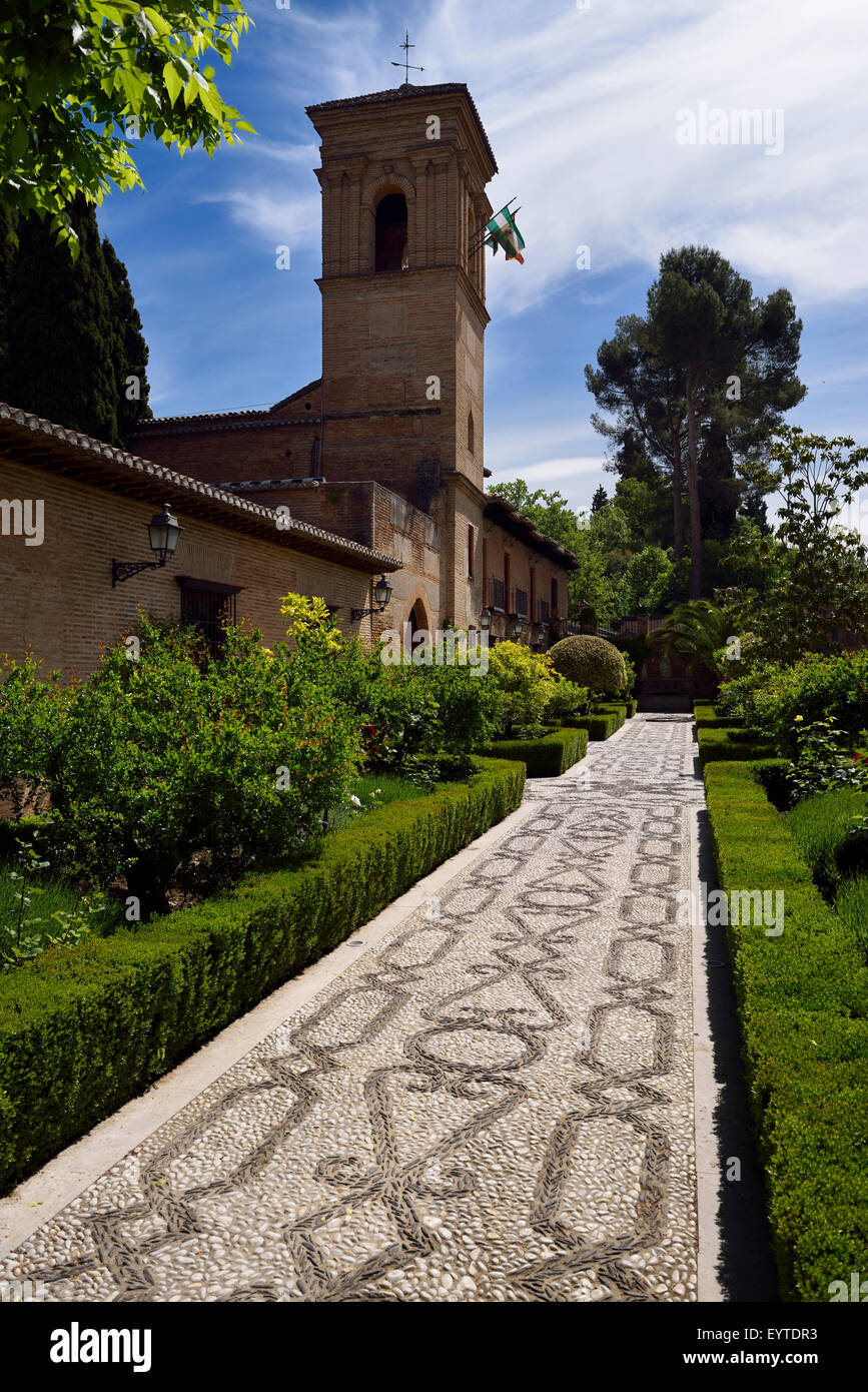 Inlaid stone patterned garden walkway of San Francisco convent with Bell Tower at Alhambra Palace Granada Spain - Stock Image