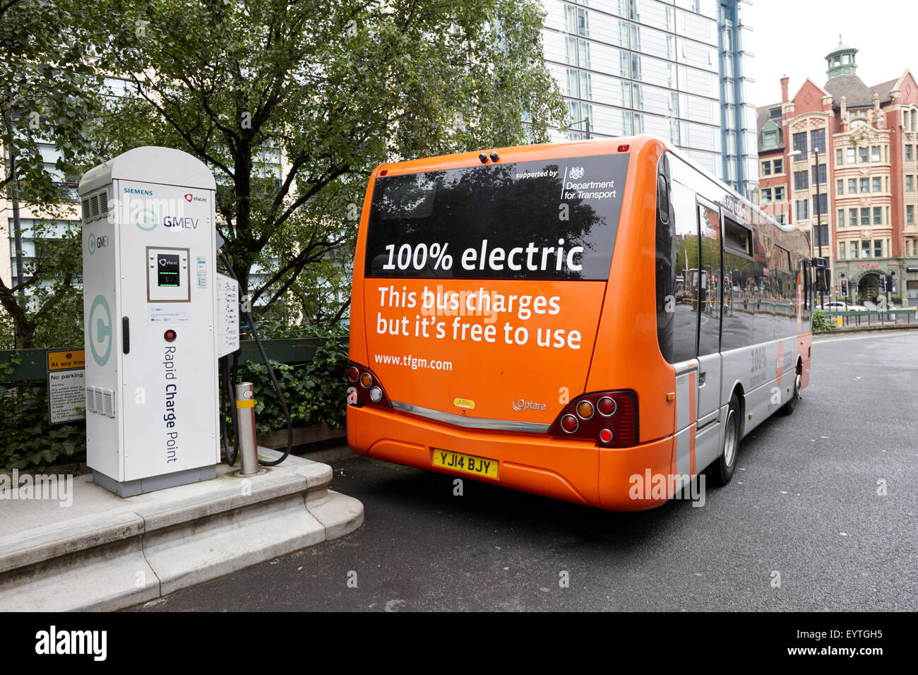 charging metro shuttle free electric bus service in Manchester city centre England UK - Stock Image