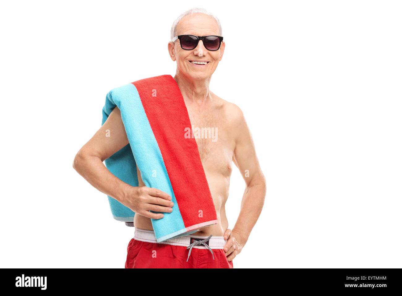 Mature tourist in swim trunks holding a towel and looking at the camera isolated on white background - Stock Image