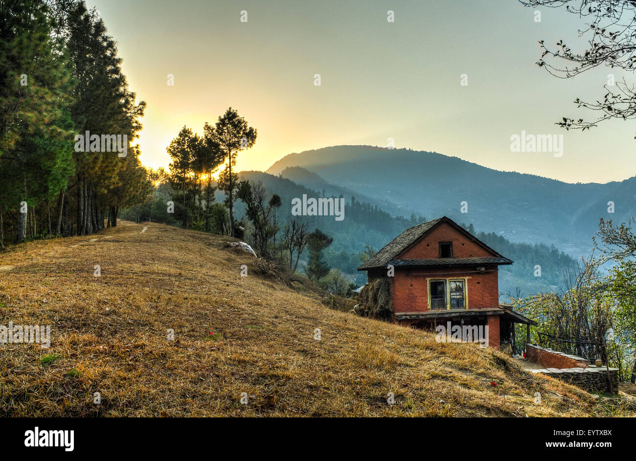 Red House Sunset. landscape shot of the setting sun behind a red hill house in Daman, Palung, Makawanpur district - Stock Image