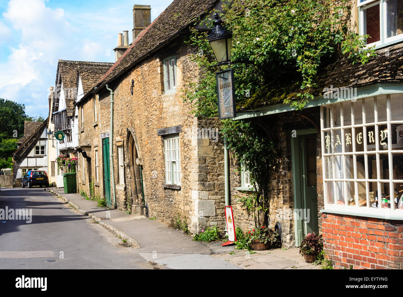 England, Lacock, Cotswolds. Church Street, 15th century - 18th century Cotswold stone buildings, tourists walking - Stock Image
