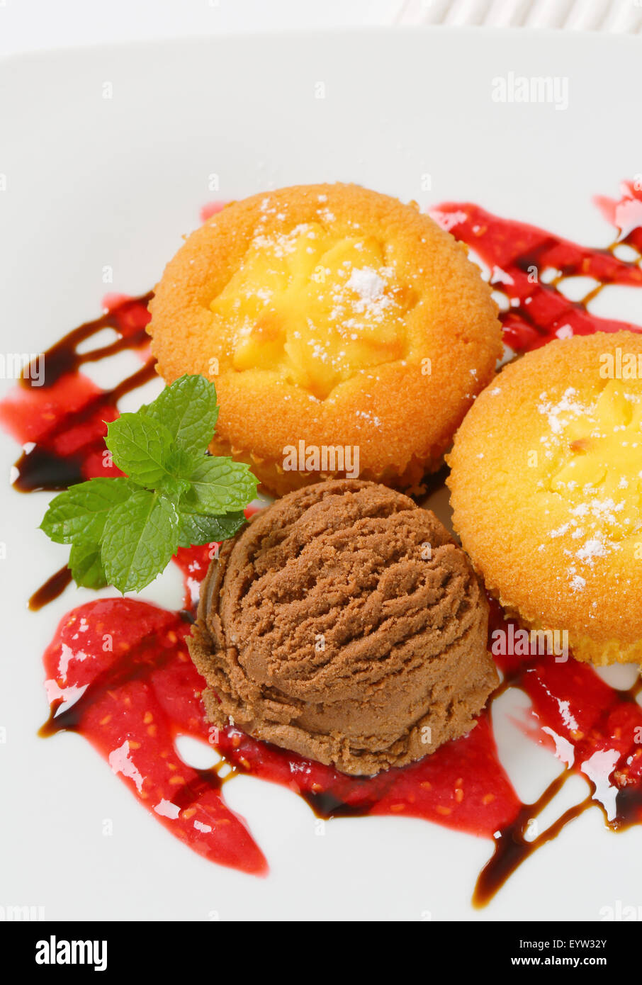 Pudding filled cupcakes and scoop of ice cream - Stock Image