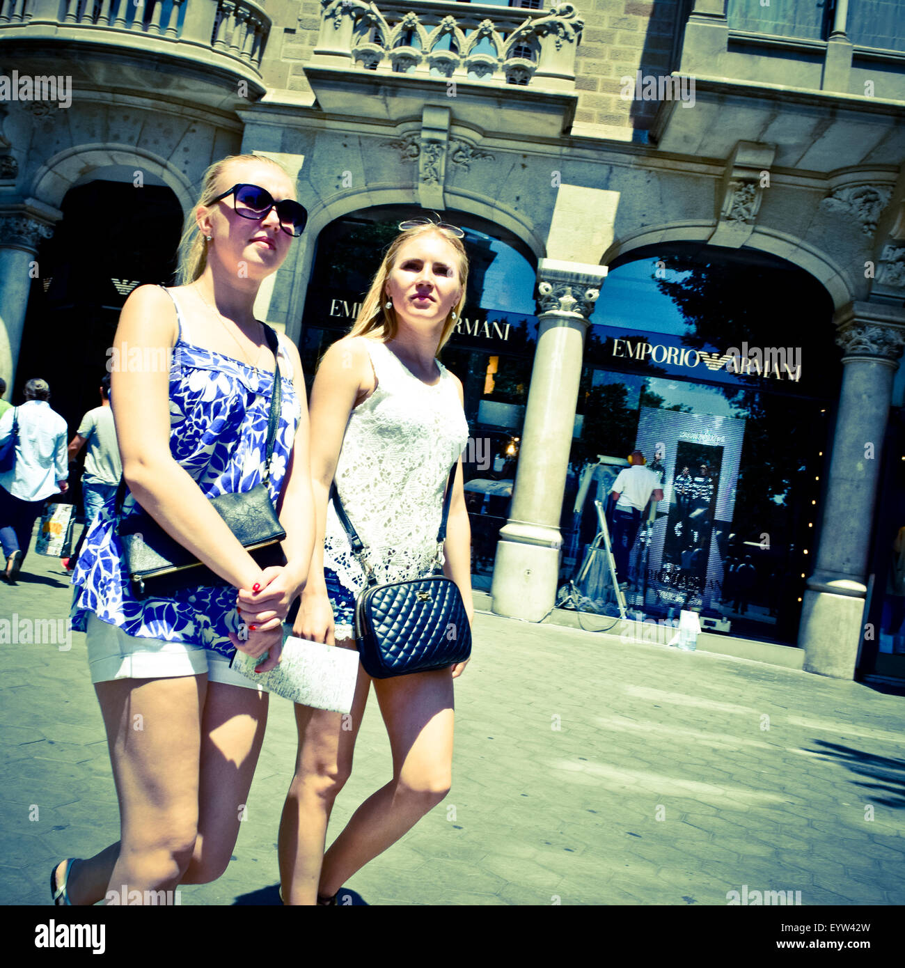 Two blond young women walking in a front of Emporio Armani store. Barcelona, Catalonia, Spain. - Stock Image