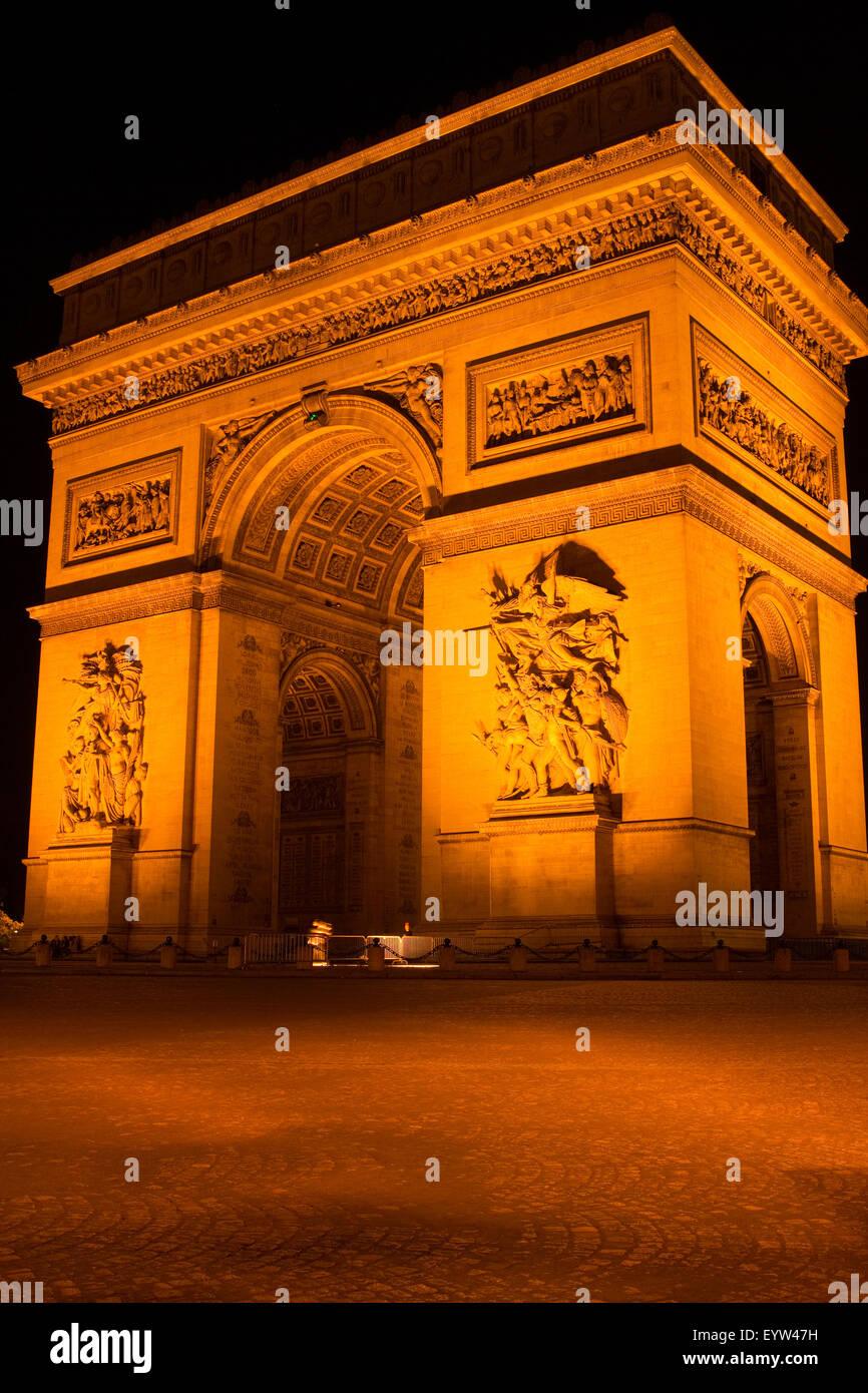 Arc de Triomphe de l'Étoile at night with no traffic. Stock Photo