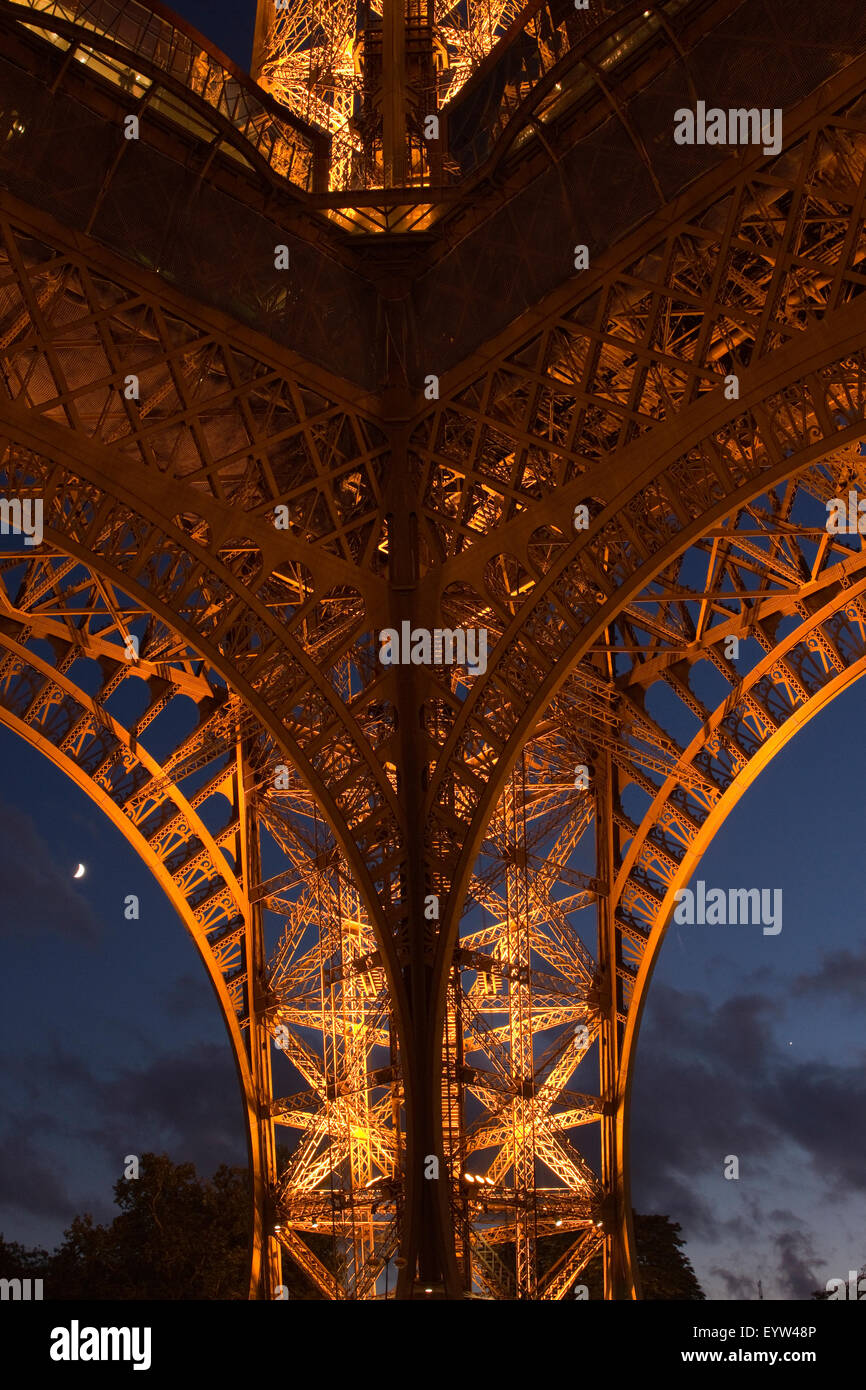Detail of the west pillar of the Eiffel Tower at night with half moon in the background. - Stock Image