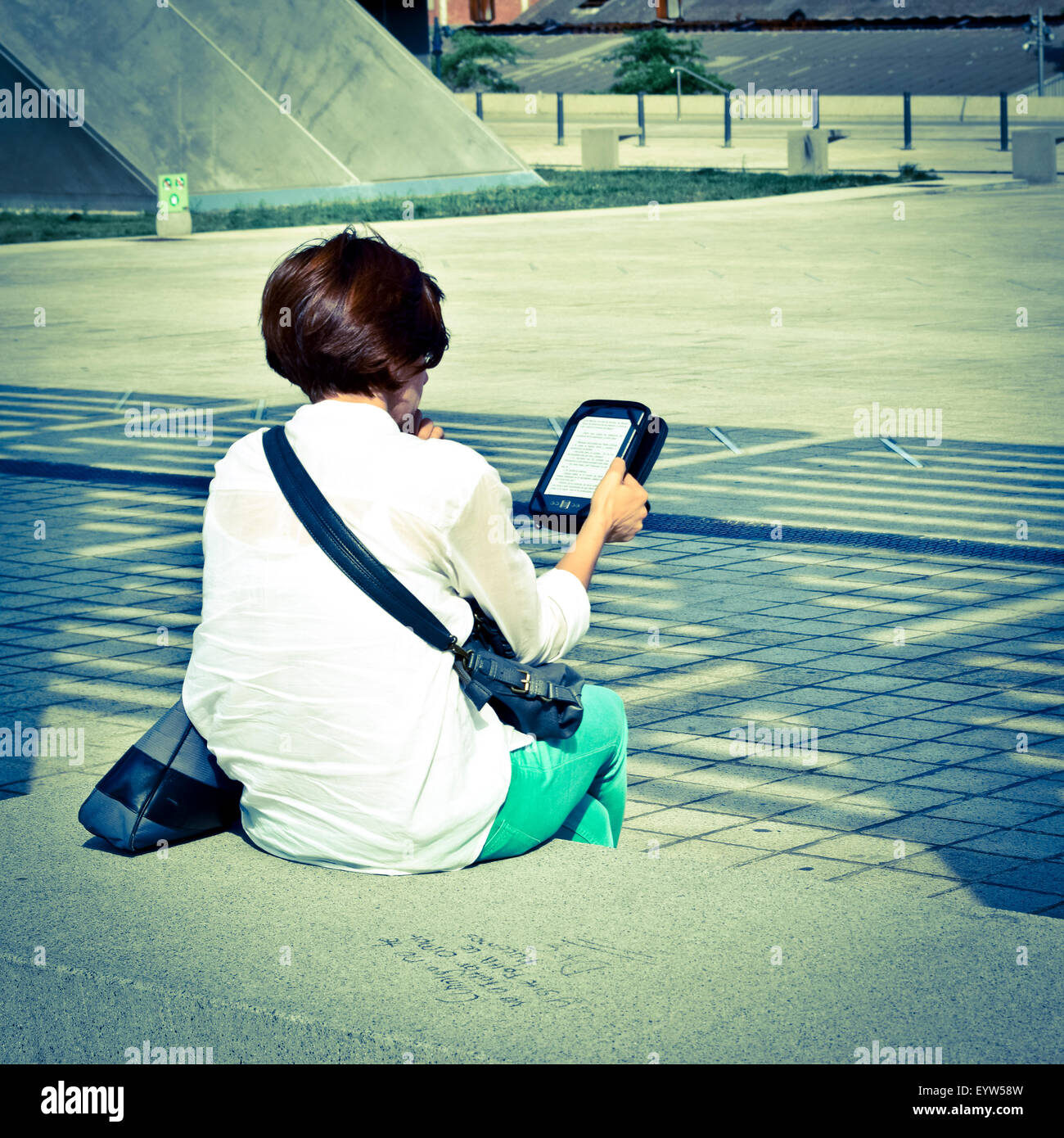 Woman sitting on a bench back. She holds an ebook device and reads. - Stock Image