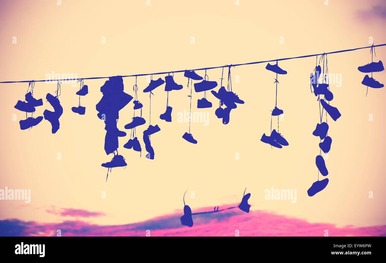 Vintage toned silhouettes of shoes hanging on cable at sunset. - Stock Image