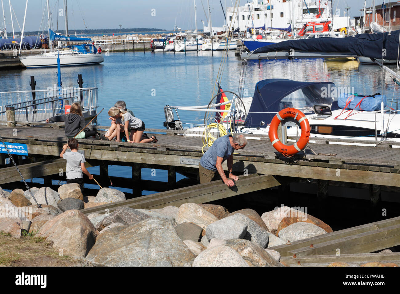 Tourist family on sailing vacation enjoy morning activities and cosy ambience at Hundested Harbour, Zealand, Denmark. - Stock Image