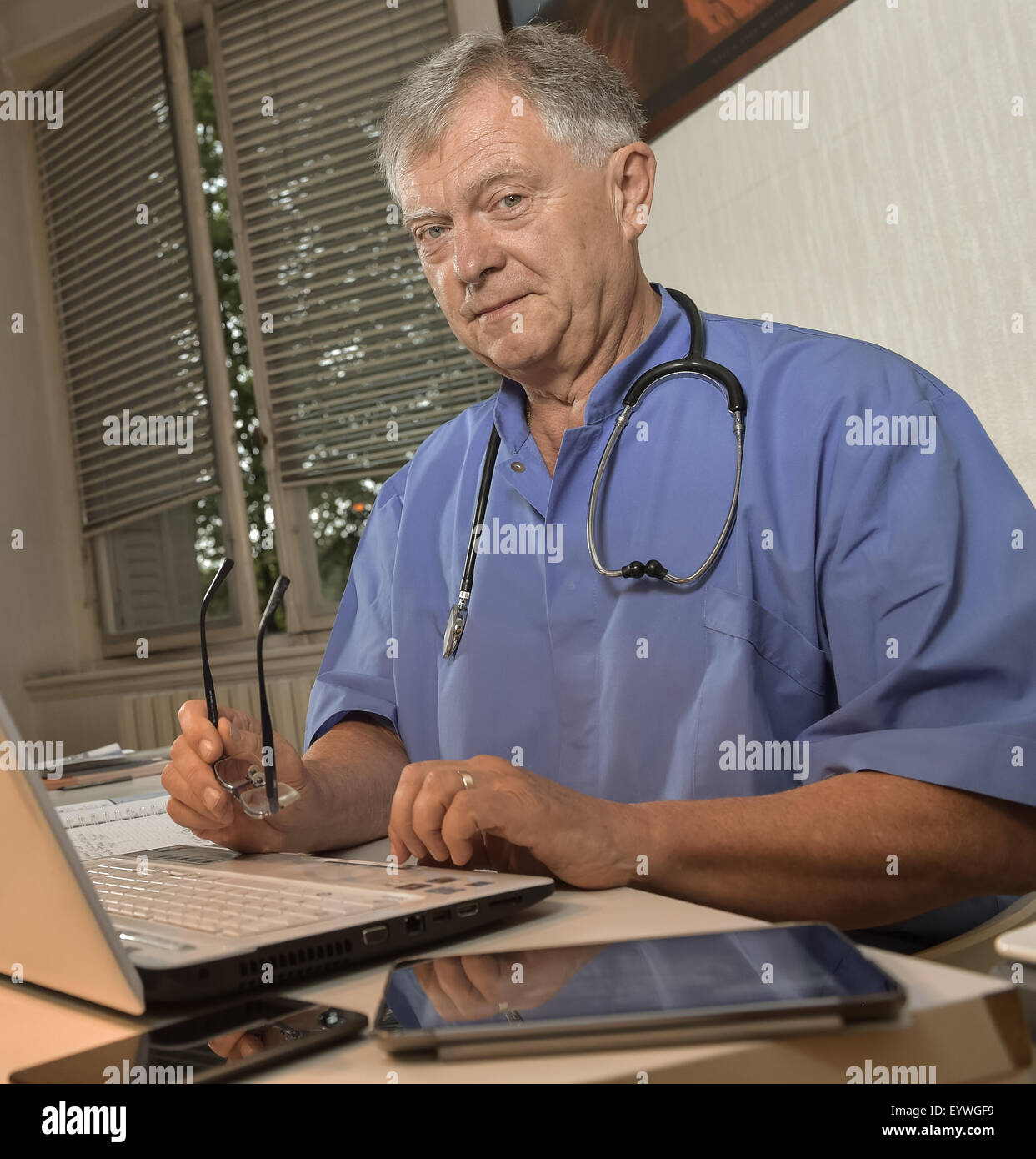 Portrait of smiling doctor at laptop in office - Stock Image