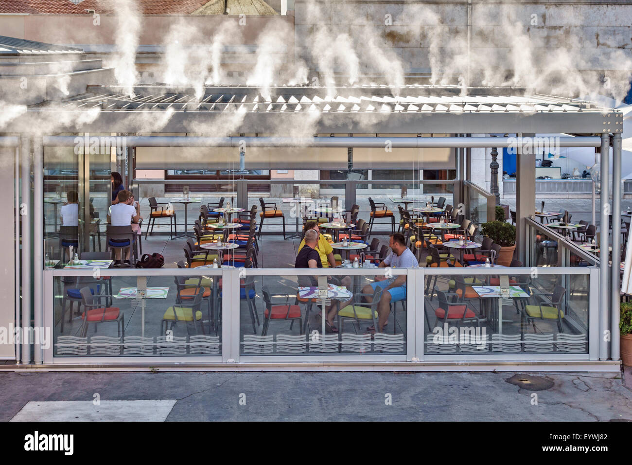 Pula, Croatia. An open-air restaurant using a water mist cooling system in summer - Stock Image