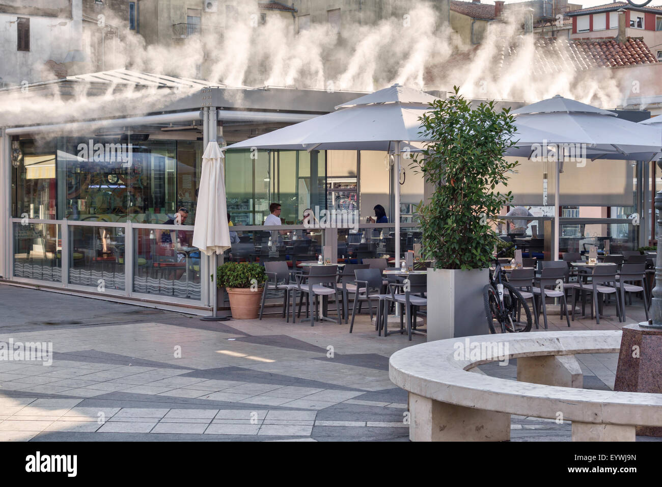 Pula, Croatia. An open-air restaurant using a water mist cooling system in summer, when 40 degree temperatures are - Stock Image