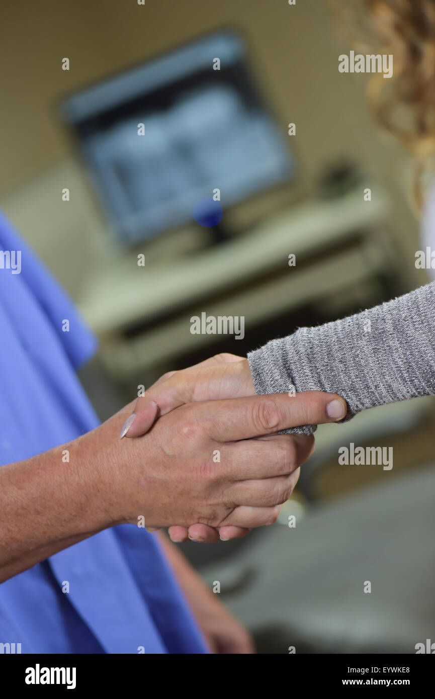 Female patient and dentist shaking hands - Stock Image