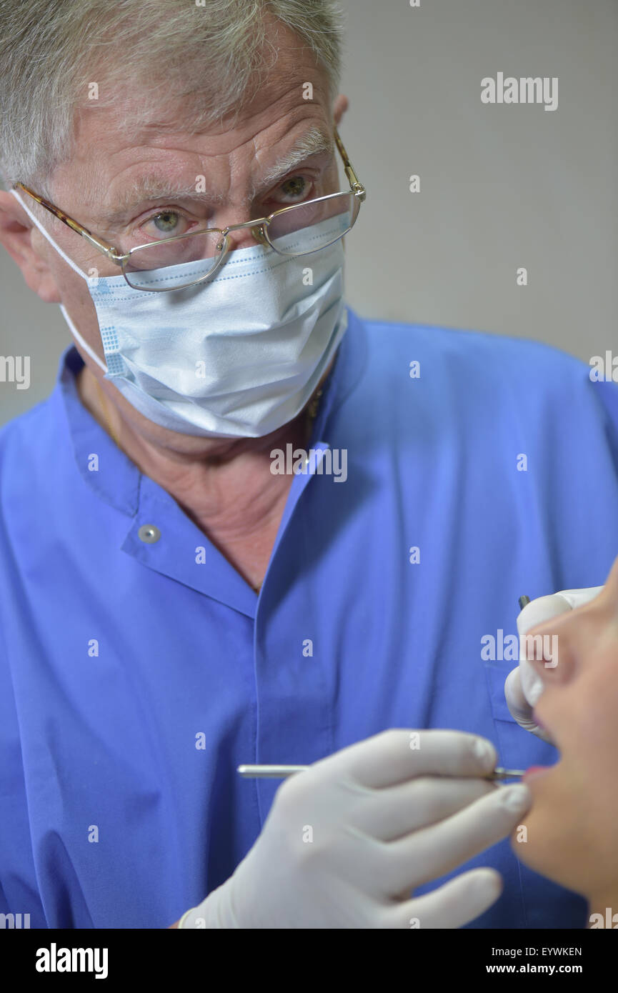 Portrait Dentist in action in office - Stock Image