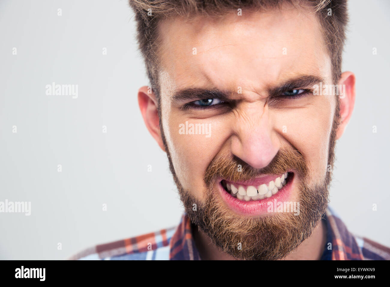 Closeup portrait of angry man looking at camera isolated on a white background - Stock Image