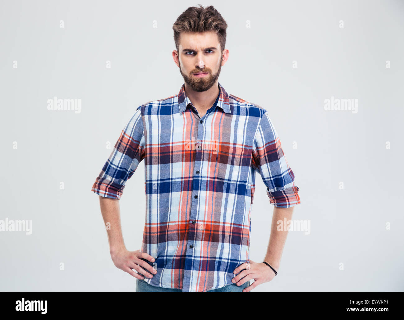 Portrait of a young serious man looking at camera isolated on a white background - Stock Image