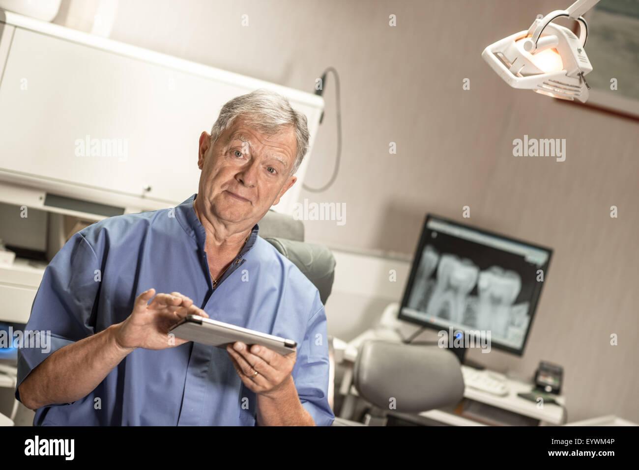 Dentist using digital tablet in office - Stock Image