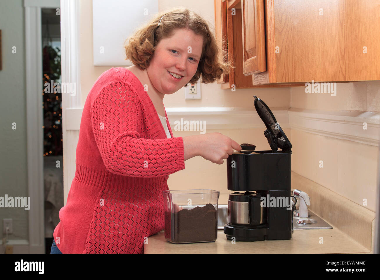 Young woman with Autism making coffee in her kitchen - Stock Image