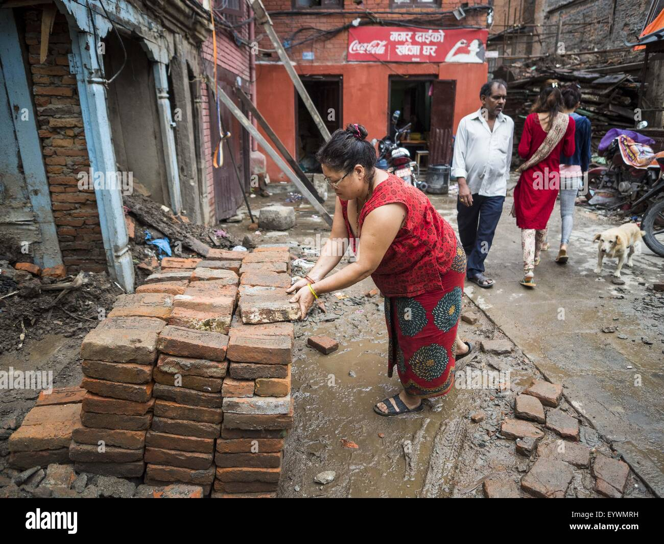 July 30, 2015 - Kathmandu, Nepal - A woman collects clay bricks for recycling and reuse around her home in Kathmandu - Stock Image