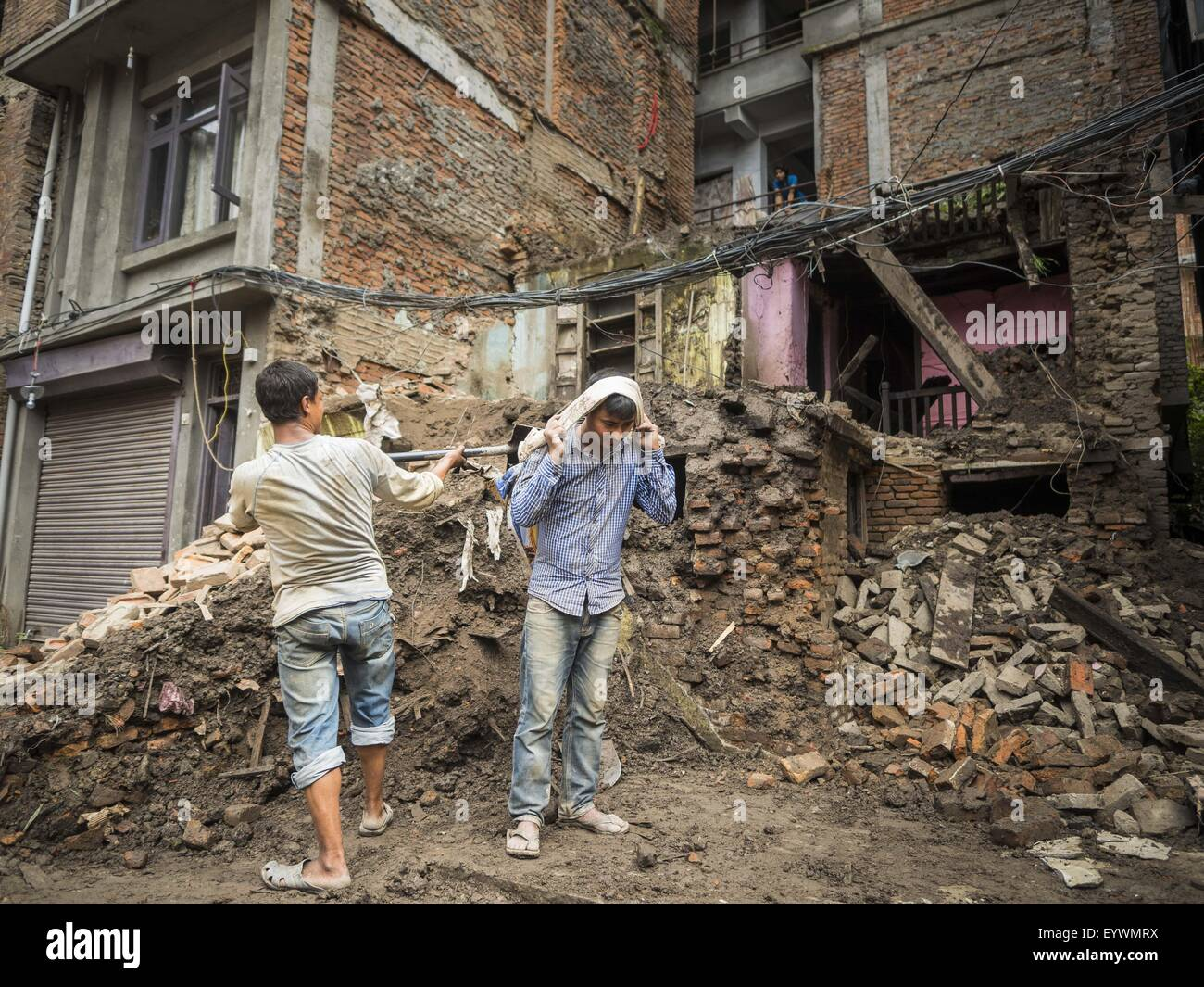 Kathmandu, Nepal. 1st Aug, 2015. Workers in Kathmandu recover bricks from of a home destroyed by the earthquake. - Stock Image