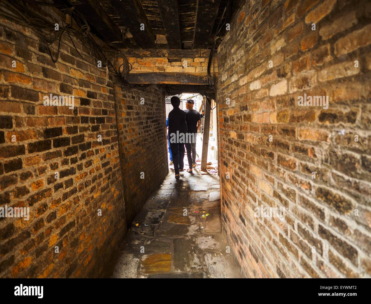 Kathmandu, Nepal. 1st Aug, 2015. A brick tunnel leads into a residential courtyard in Kathmandu. After earthquake, - Stock Image