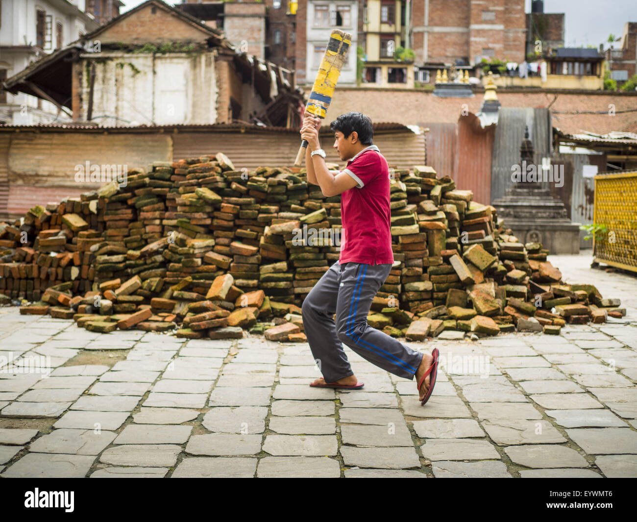 Kathmandu, Nepal. 1st Aug, 2015. Boys practice cricket batting in front of a pile of bricks recovered for earthquake - Stock Image